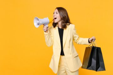 Funny young woman 20s in basic light suit jacket hold package bags with purchases after shopping screaming in megaphone looking aside isolated on yellow background, studio portrait. Black friday sale.