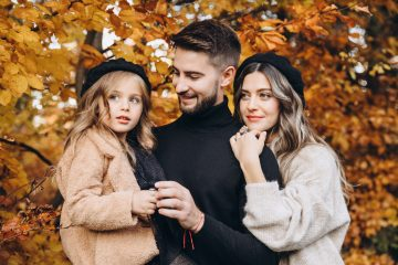 Stylish family in the autumn forest. Models. A young guy and a girl stand on a forest road among yellow leaves and hold their daughter in their arms.